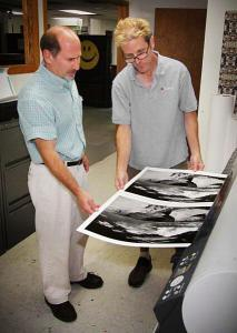 Two men looking at newly printed photos on canvas